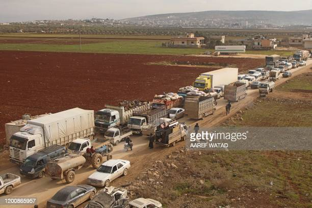 A large convoy of displaced Syrians who fled proregime offensive on the last major rebel bastion in the country's northwest drive through the town of...