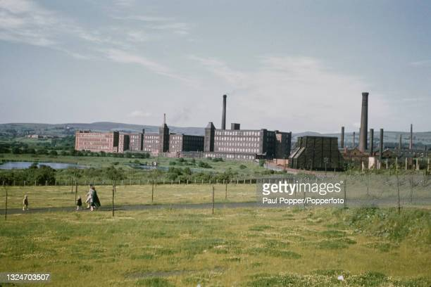 Large cotton and textile mills and associated factory chimneys stand near the River Irwell in the town of Bury near Manchester, England circa 1960.