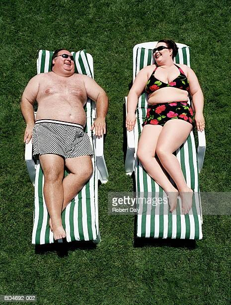 Large couple relaxing on sun loungers, smiling, elevated view