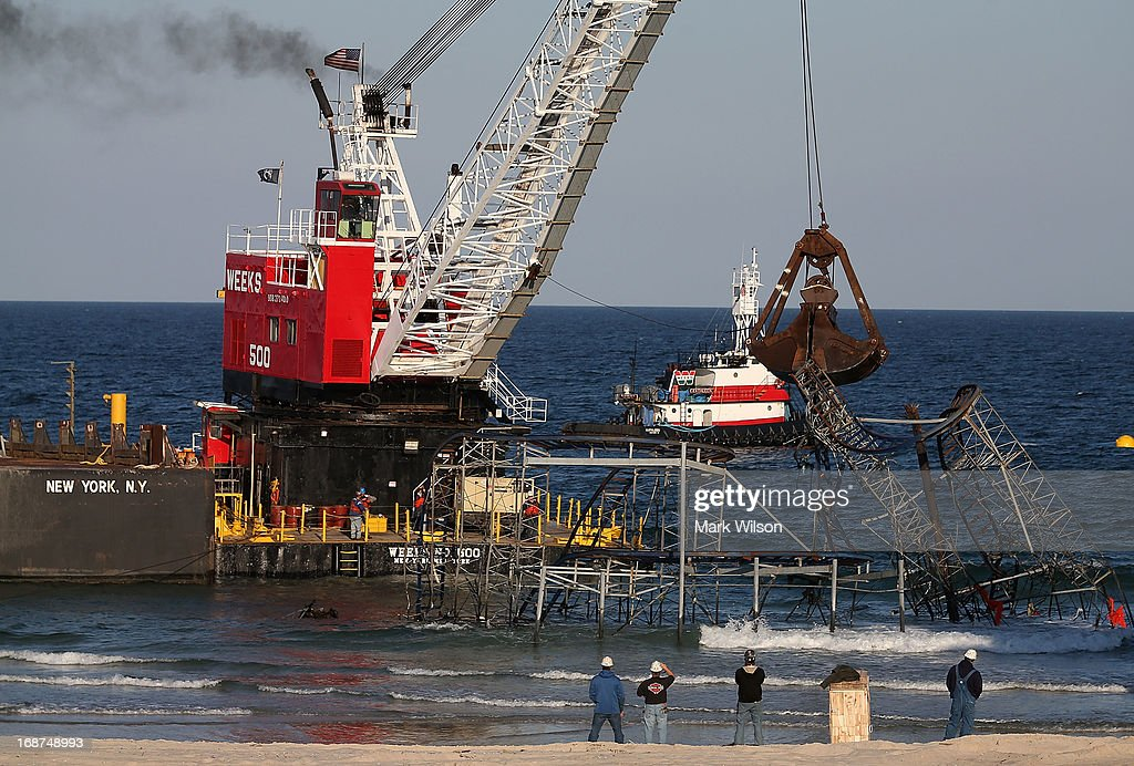 A large crane demolishes the JetStar roller coaster that has been in the ocean for six months after the Casino Pier is sat on collapsed when Superstorm Sandy hit, May 14, 2013 in Seaside Heights, New Jersey. The Casino Pier has contracted Weeks Marine to remove the JetStar roller coaster from the Atlantic Ocean.