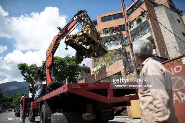 Large crane helps lift a water drill rig trailer over the wall of a residential building during the construction of a water well of a depth of 90...