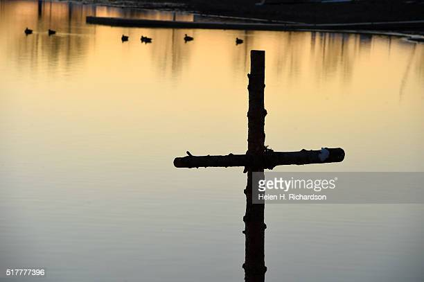 A large cross made from the wood of the church's Christmas tree is put in the sand for the 21st annual Easter sunrise celebration service on the...