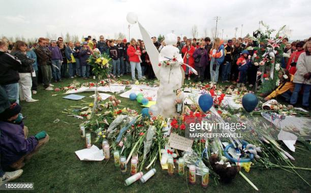 A large crowd circles an angel made of snow leaving flowers during a memorial service 25 April 1999 in rememberance of the students who were killed...