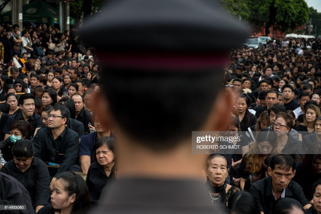 TOPSHOT - A large crowd clad in black who came to pray for the late Thai King Bhumibol Adulyadej is watched by a Thai policeman in front of the Grand Palace in Bangkok on October 16, 2016. On his birthday Thais wore yellow, when he got sick they put on pink, and now that King Bhumibol Adulyadej has passed Bangkok's streets have turned monochrome in a extraordinary display of collective grief. / AFP / ROBERTO