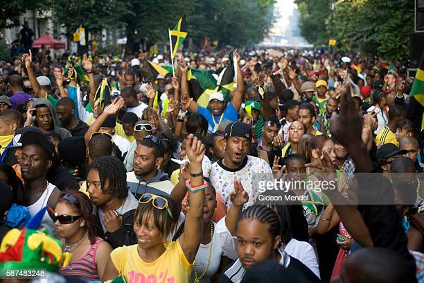 A large crowd dances to reggae music and wave Jamaican flags during the Notting Hill Carnival This is an annual event which has taken place on the...