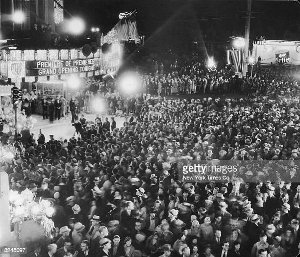 A large crowd gathered outside the Warner Brothers movie theatre on Wilshire Boulevard in Los Angeles for a night opening The sign outside the cinema...