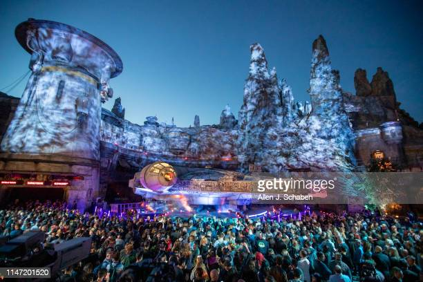 Large crowd gathers in front of the Millennium Falcon at dusk during the Star Wars: Galaxy's Edge unveiling event at the Disneyland Resort in...