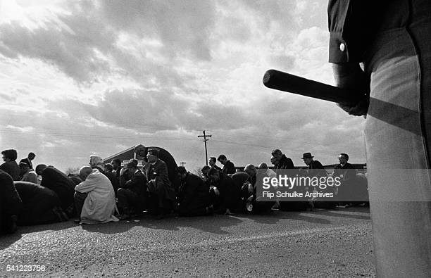 A large crowd of civil rights marchers kneel to pray after crossing the Edmund Pettus Bridge in Selma A policeman stands nearby with his billy club...