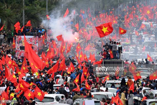 A large crowd of football fans wave the national flag as they follow a bus carrying the members of the U23 Vietnamese National team through the...