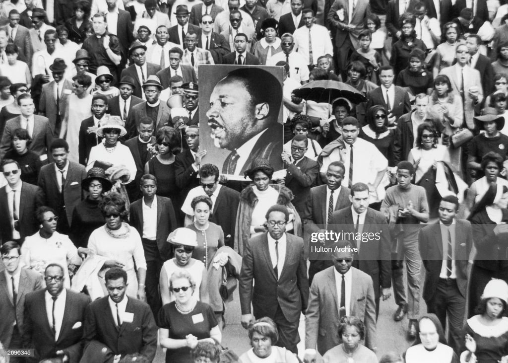 A large crowd of mourners follow the casket of Dr Martin Luther King Jr through the streets of Atlanta, Georgia. Two men carry a large sign with King's face.