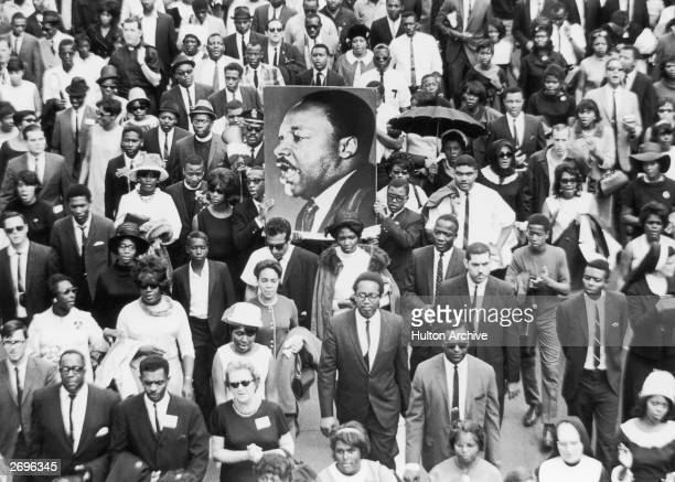 A large crowd of mourners follow the casket of Dr Martin Luther King Jr through the streets of Atlanta Georgia Two men carry a large sign with King's...