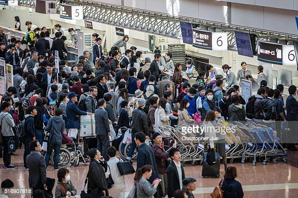 A large crowd of passengers queue at All Nippon Airways checkin counters at Haneda Airport on March 22 2016 in Tokyo Japan A failure with the checkin...