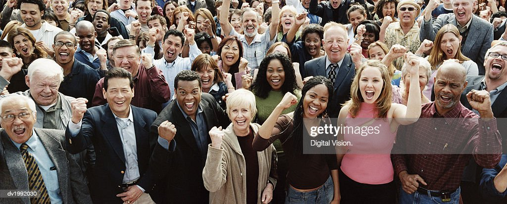 Large Crowd of People Cheering and Raising Their Fists : Stock Photo
