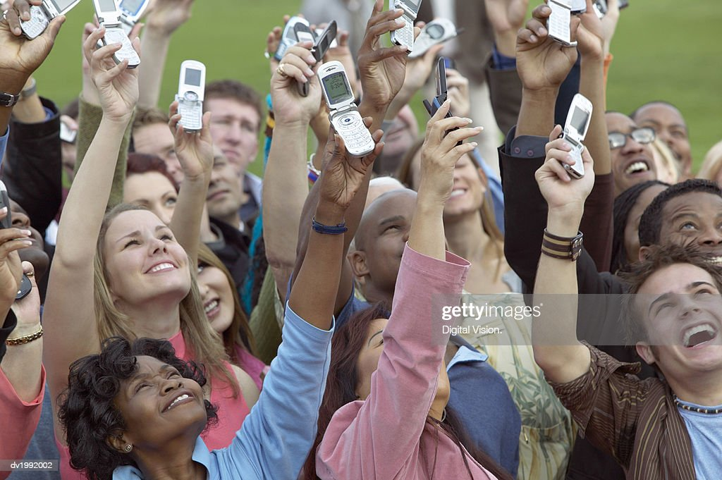 Large Crowd of People Holding Mobile Phones in the Air : Stock Photo