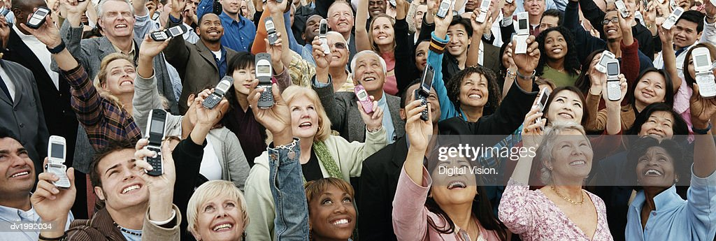 Large Crowd of People Holding Their Mobile Phones in the Air : Stock Photo