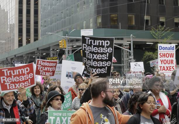 A large crowd of people march holding signs during a March On Tax Day to demand that United States President Donald Trump release his tax returns at...