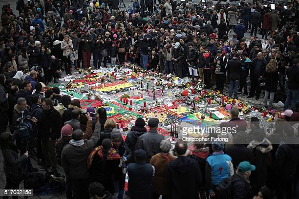 A large crowd of people view tributes at Place De La Bourse in honour of the victims of yesterdays' terror attacks on March 23 2016 in Brussels...