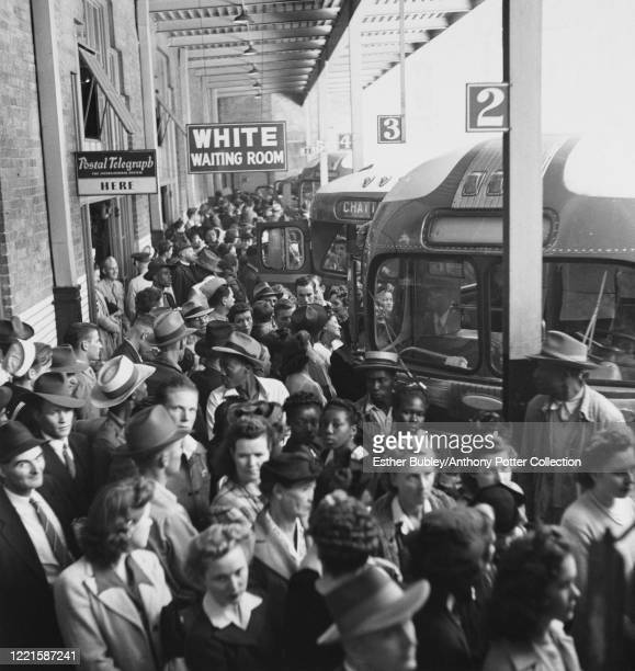 Large crowd of people waiting to board a bus at a station in Memphis, Tennessee, US, September 1943.
