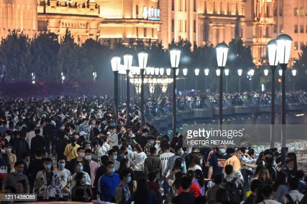 TOPSHOT Large crowd of people wearing face masks visit the promenade on the Bund along the Huangpu River during a holiday on May Day or International...