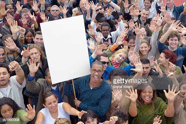 large crowd of people with their hands raised in the air with one man holding a blank placard - manifestación fotografías e imágenes de stock
