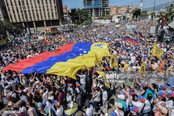 Large crowd of president Juan Guaido's supporters seen holding a huge Venezuelan flag during a protest against Maduro Opposition supporters take part...
