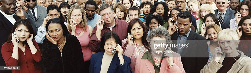 Large Crowd of Serious People Using Mobile Phones : Stock Photo