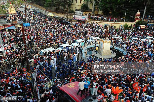 A large crowd of supporters cheer for India's election frontrunner as his convoy passes by an intersection of Varanasi on May 8 2014 Tens of...
