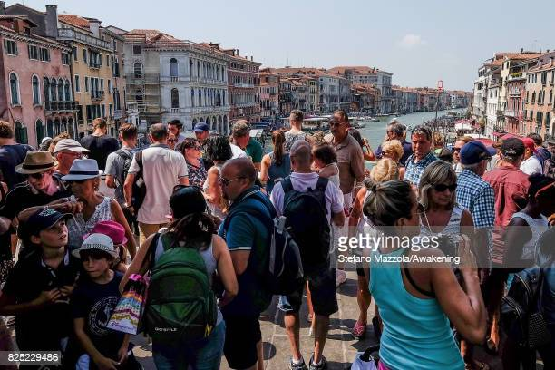 A large crowd of tourists stand on Rialto bridge on August 1 2017 in Venice Italy Over 30 million tourists visit the 3 mile by 2 mile city of Venice...