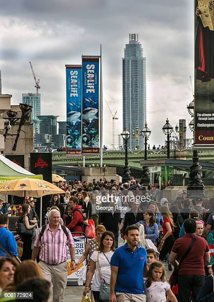 A large crowd of tourists walk along 'The Queen's Walk' located under the London Eye as viewed from Westminster Bridge on September 9 in London...