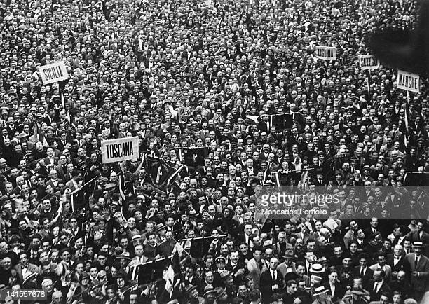 A large crowd participating in a fascist demonstration raising placards with the name of several Italian regions Italy 1930s