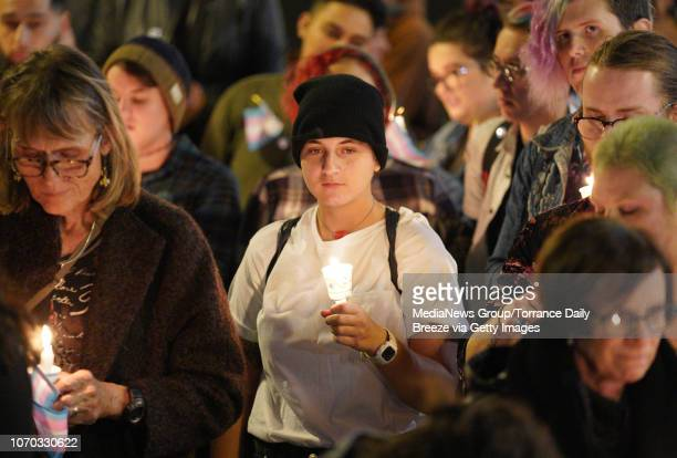 A large crowd stands with their candles and thoughts as the names of transgender people who were killed in the past year are read at the annual...