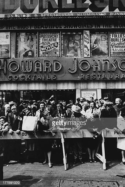 A large crowd waits behind a police line outside a Howard Johnson's restaurant and 'Follies Burlesk' on 46th St and Broadway New York City circa 1970