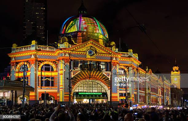 CONTENT] Large crowds gather outside Flinders Street Station as a design inspired by Luna Park is projected onto its facade as part of White Night...