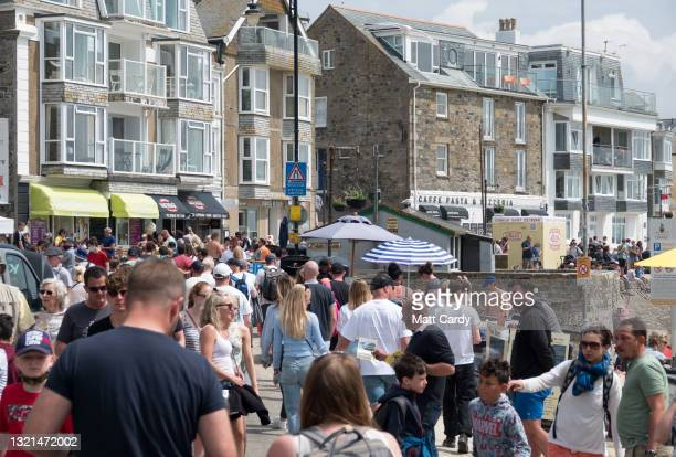 Large crowds of people gather around the harbour at the popular tourist seaside town of St Ives, close to The Carbis Bay Estate hotel and beach,...
