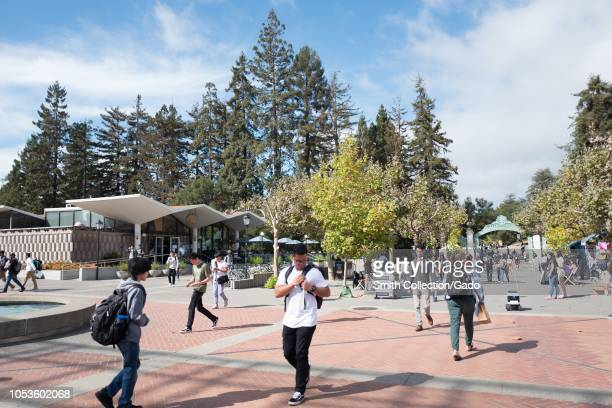 Large crowds of students walk through the campus of UC Berkeley in downtown Berkeley California on Sather Road with a Kiwi autonomous food delivery...