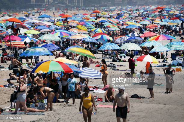 Large crowds visit the beach at Coney Island in Brooklyn on July 19, 2020 in New York City. Much of the East Coast is experiencing usually warm...