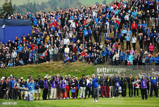Large crowds watch Victor Dubuisson of Europe play a shot from the fairway during the Singles Matches of the 2014 Ryder Cup on the PGA Centenary...