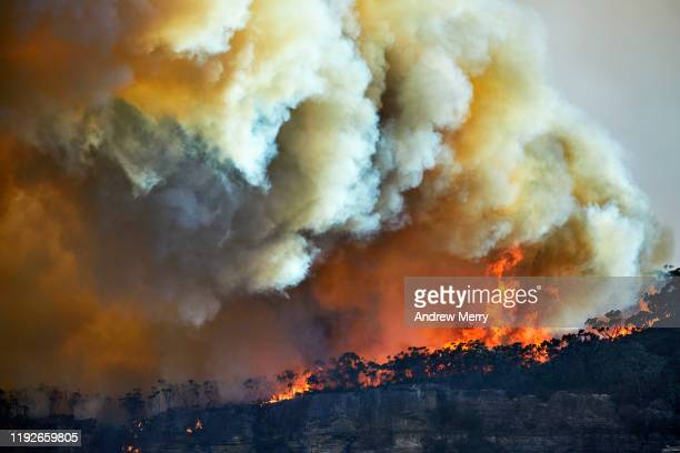 large dark smoke cloud from wildfires, bush fires on mountain, air pollution, climate change in australia - smog stock pictures, royalty-free photos & images