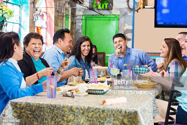 Large diverse family having dinner together in local Mexican restaurant