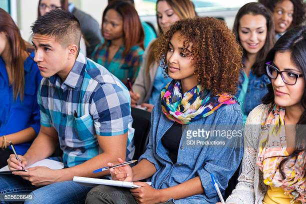 Large diverse group of teens taking notes during lecture
