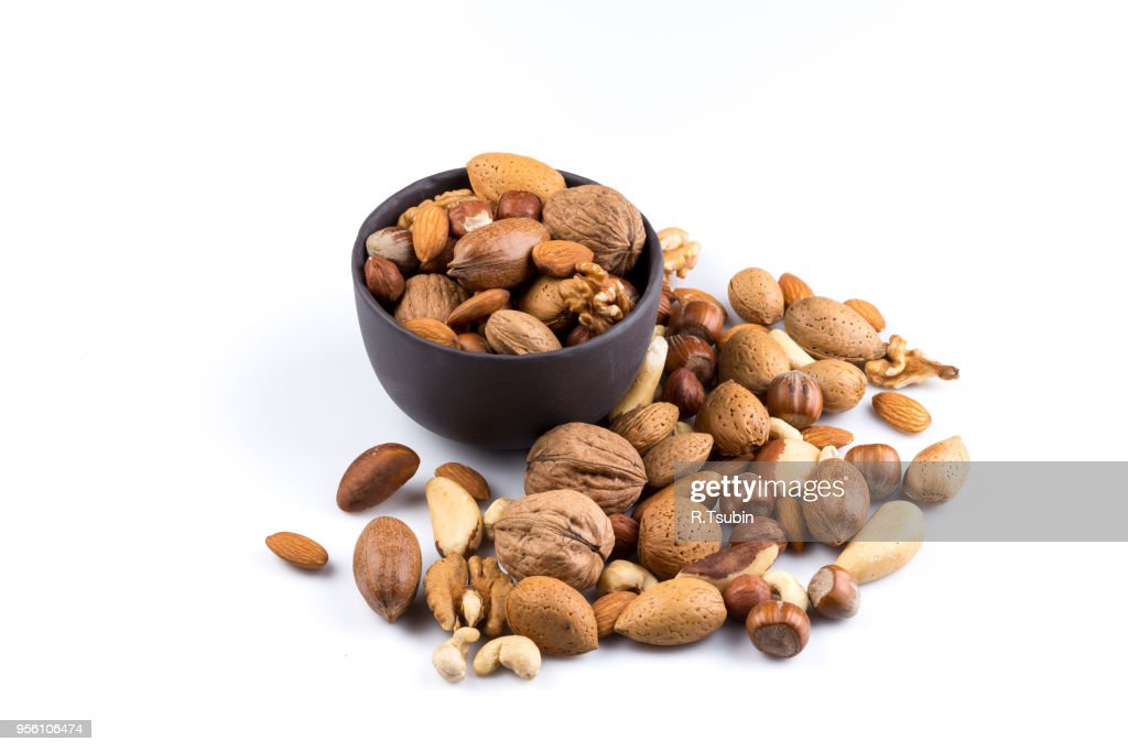 Large diversity of healthy nuts in a dark stone bowl - isolated : Stockfoto