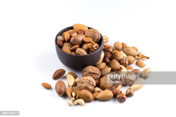 large diversity of healthy nuts in a dark stone bowl - isolated - ナッツ類 ストックフォトと画像