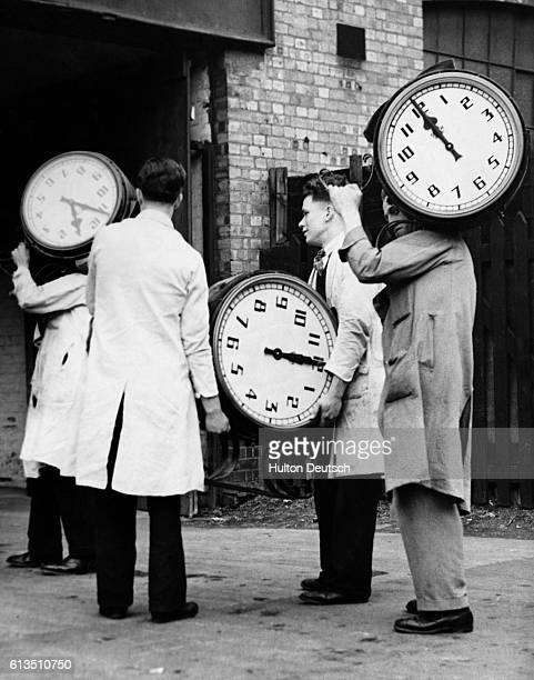 Large electric clocks are being carried into a factory in London in 1936