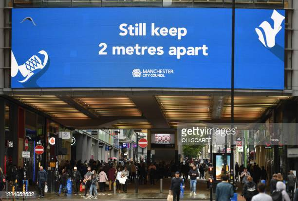 A large electronic sign reminds people to maintain a 2metre social distance in the centre of Manchester northwest England on July 4 as restrictions...