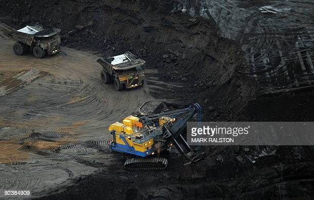 A large excavator loads a truck with oil sands at the Suncor mine near the town of Fort McMurray in Alberta Province Canada on October 23 2009...