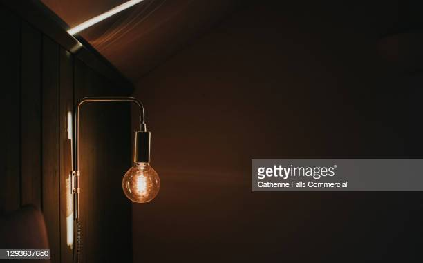 large exposed wall mounted lightbulb - electric light stock pictures, royalty-free photos & images