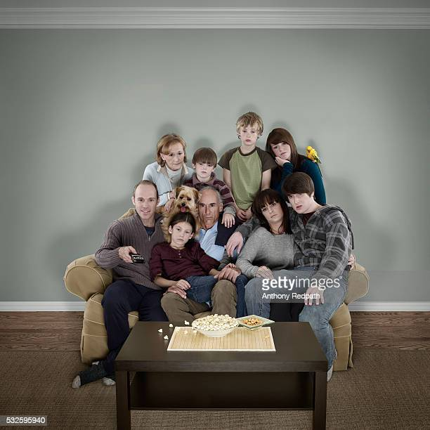 A large family on a small couch watching television
