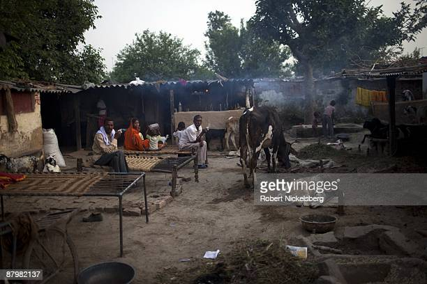 A large family sits in a slum area near a newly dug roadway April 21 2009 where agricultural areas they and members of twelve families have been...