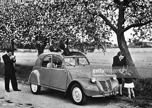 Large family travelling with a Citroen 2 CV circa 1950 in France