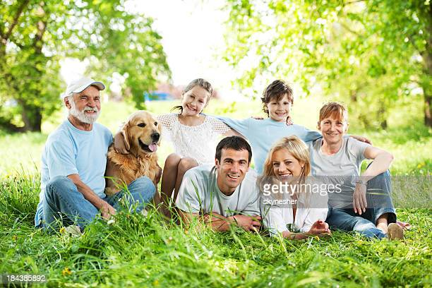 Large family with grandparents sitting in the grass.